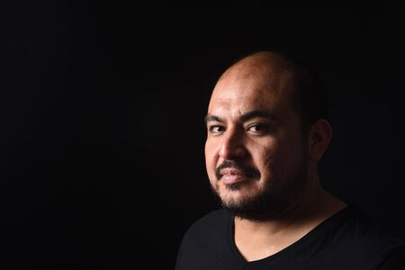 portrait of a latin american man on black background