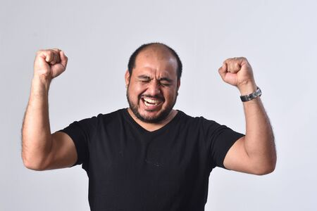 latin american man raising her arms and smiling in victory sign on white background