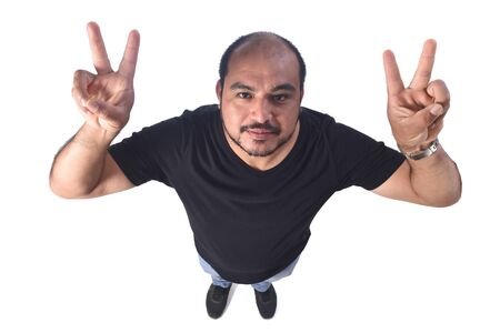 Latin american man making the victory sign on a white background