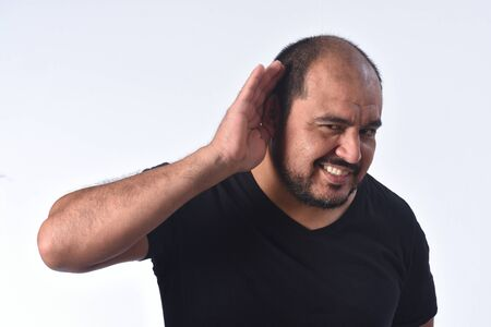 latin american man putting a hand on her ear because she can not hear on white background Zdjęcie Seryjne