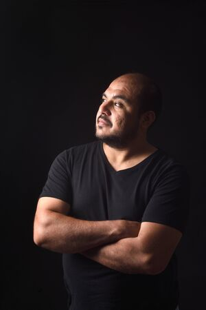 portrait of profile of a latin american man arms crossed on black background, serious