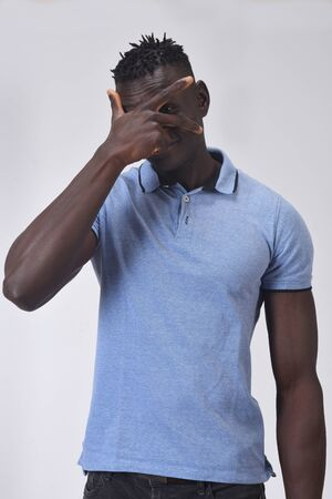 african man peeking with hand on face on white background