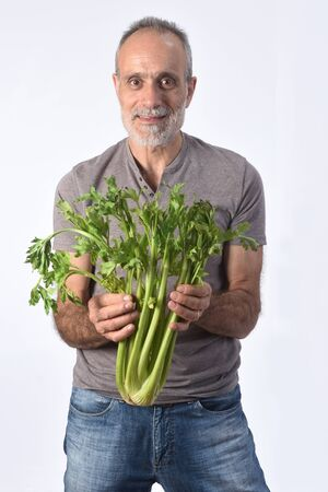 portrait of a man with celery on white background Foto de archivo