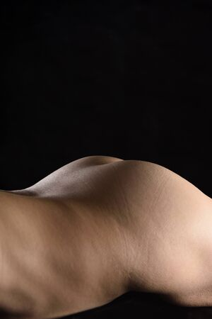 curves of a woman lying on black background