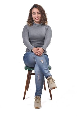 portrait of a woman sitting on a chair in white background, looking at camera and legs crossed Stock Photo