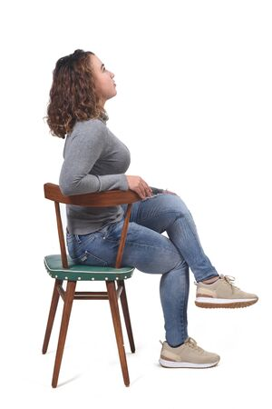 portrait of a woman sitting on a chair in white background, rear view of the chair and looking up