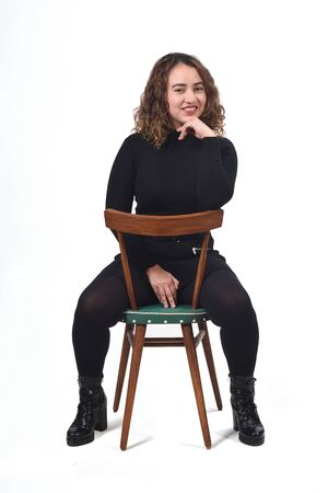 portrait of a woman sitting on a chair in white background,hand on chin