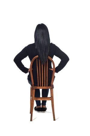 rear view of a woman sitting on chair on white background, hand on hip