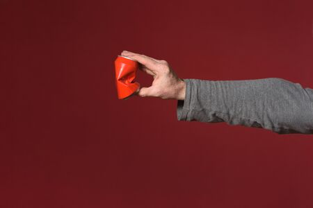 hand crushing a can of drink on red background Standard-Bild