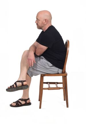 Bald man with sandals t-shirt and shorts sitting on white background, side view, Stock Photo