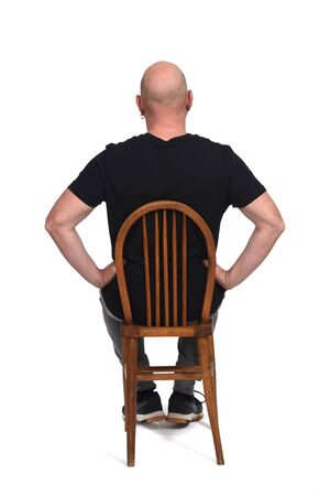 rear view of a bald man siiting on a chair with sportiswear on white background, hands on hip Imagens