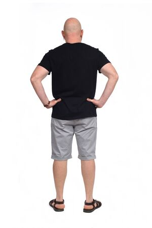 rear view of bald man with sandals t-shirt and shorts on white background, hands on hip