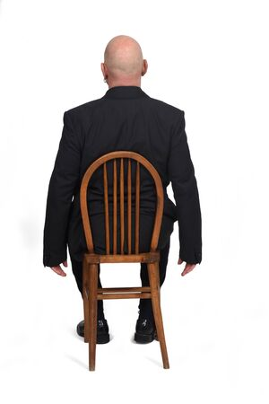 man sitting on a chair with her back on white background,