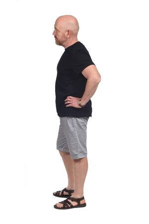homme chauve de profil avec chemise short et sandales, main sur la hanche