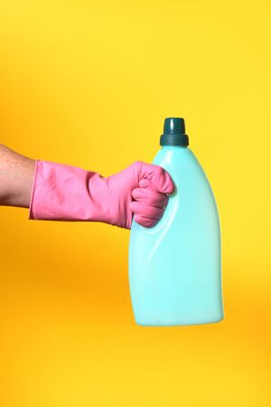 hand with glove and plastic bottle soap on yellow background