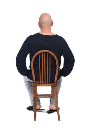 rear view of a man in pajamas sitting o a chair on white background,  版權商用圖片