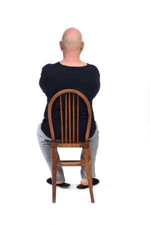 rear view of a man in pajamas sitting o a chair on white background,  arms crossed, 版權商用圖片 - 150657685