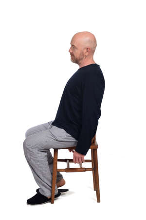 man in pajamas sitting on a chair on white background, side view