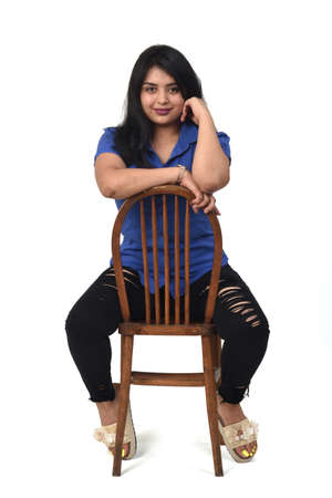 Portrait of a Latin woman sitting on a chair on white background, looking at camera 版權商用圖片 - 155047152