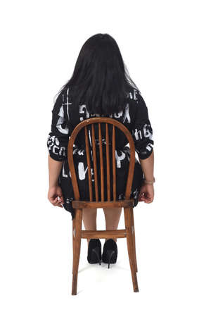 latin woman with dress and high heels sitting looking at camera on chair on white background, arms crossed and looking at camera 版權商用圖片 - 155047158