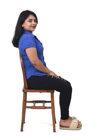 latin woman with dress and high heels sitting looking at camera on chair on white background, arms crossed and looking at camera 版權商用圖片 - 155047178