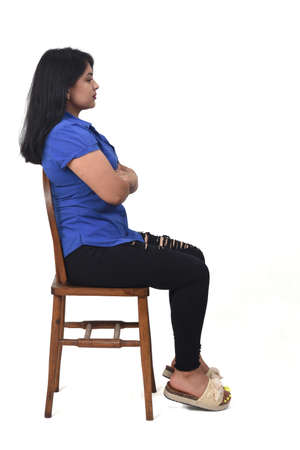 latin woman with dress and high heels sitting looking at camera on chair on white background, arms crossed and looking at camera 版權商用圖片 - 155047179