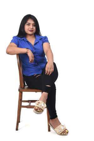 latin woman with dress and high heels sitting looking at camera on chair on white background, arms crossed and looking at camera 版權商用圖片