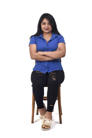 latin woman with dress and high heels sitting looking at camera on chair on white background, arms crossed and looking at camera 版權商用圖片 - 155047190