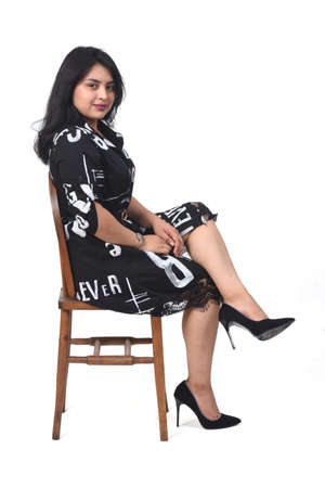 latin woman with dress and high heels sitting looking at camera on chair on white background, arms crossed and looking at camera 版權商用圖片 - 155047195
