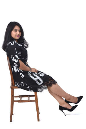 side view of latin woman with dress and high heels sitting on chair on white background, relaxed 版權商用圖片 - 155047199