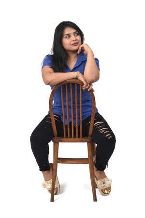 Portrait of a Latin woman sitting on a chair that is turned on white background, look up 版權商用圖片 - 155047243