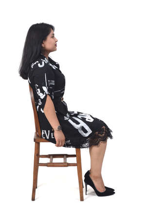 side view of latin woman with dress and high heels sitting on chair on white background, 版權商用圖片 - 155047260