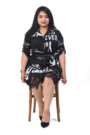 front view of latin woman with dress and high heels sitting on chair on white background 版權商用圖片 - 155047263