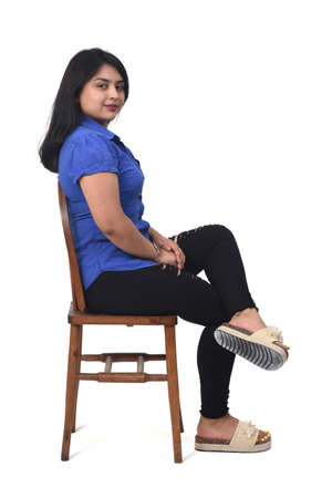 portrait of a latin woman sitting on a chair in white background, side view, looking at camera and arms crossed 版權商用圖片 - 155047266