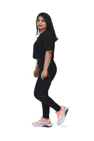 side view of a latin woman walking with sportswear looking at camera on white background, 版權商用圖片 - 155047271