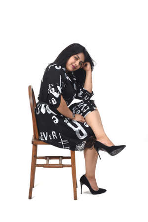 sideways of latin woman with dress and high heels on white background, arms crossed