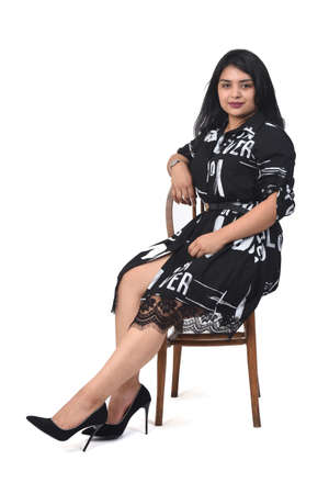 rear view of a woman sitting on a chair and looking at camera on white background,