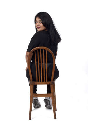rear view of a woman sitting on a chair and looking at camera on white background, 版權商用圖片 - 155047319