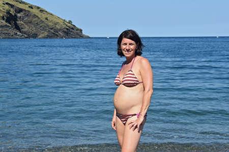 low angle of a pregnant woman sunbathing on the beach 版權商用圖片 - 155806913