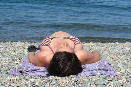 low angle of a pregnant woman sunbathing on the beach 版權商用圖片 - 155726569