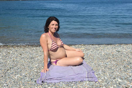 low angle of a pregnant woman sunbathing on the beach 版權商用圖片 - 155806871