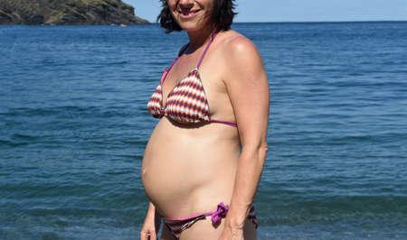 low angle of a pregnant woman sunbathing on the beach 版權商用圖片 - 155727446