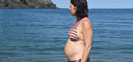 low angle of a pregnant woman sunbathing on the beach