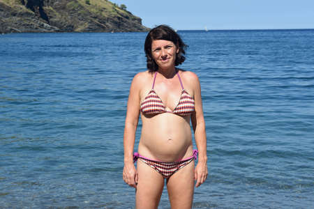 pregnant woman standing on the beach,look side