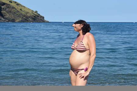 pregnant woman standing on the beach,look side 版權商用圖片 - 155727107