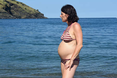 pregnant woman standing on the beach,look side 版權商用圖片 - 155807165
