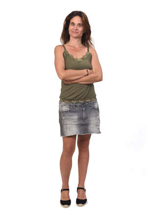 front view of the full portrait of a woman in a denim skirt on white background, hands on pocket