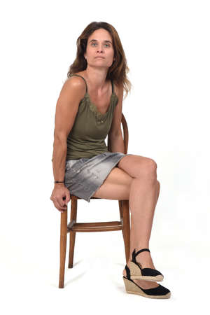 side view of a woman in denim skirt sitting on a chair and looking at camera on white background Zdjęcie Seryjne