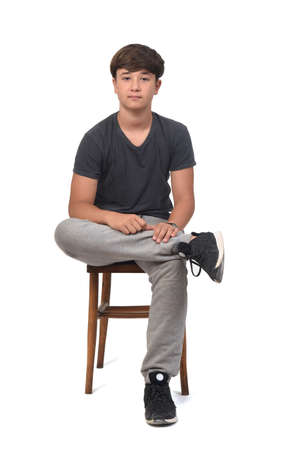 teenager boy wearing sportswear standing on white background,rear view and looking at camera