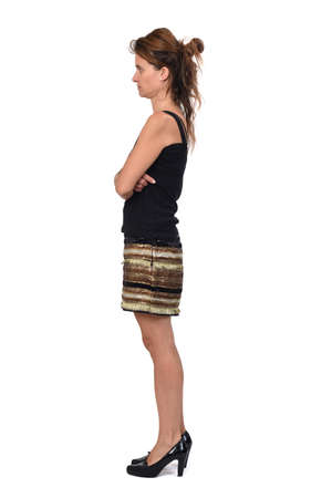 full portrait of a woman with skirt on white background, side view and arms crossed